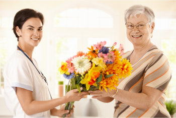 caregiver and patient holding flowers